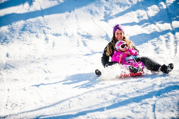 An image of a mother and child tobogganing near the Avenue Hotel in Winter