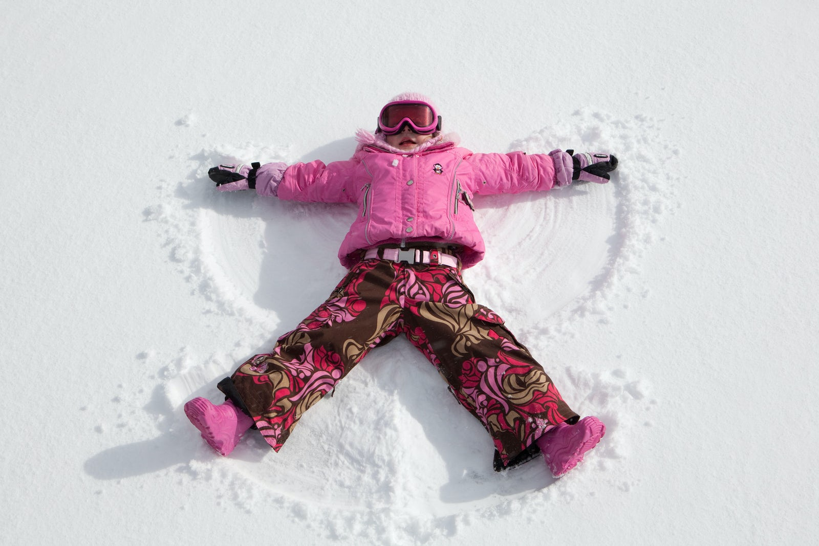 An image of a child playing in snow near the Aria Hotel in winter