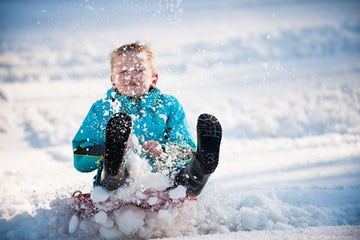 An image of a a child playing in snow at the Pavilion on Northbourne in Dickson