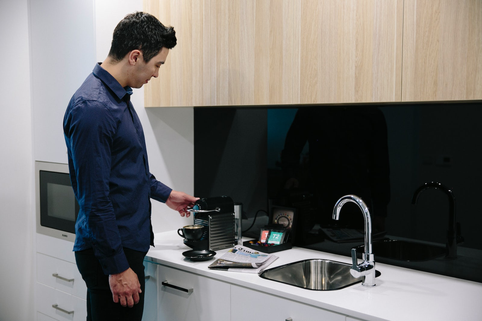 A picture of a man making coffee in his apartment at the Avenue Hotel on Northbourne Avenue