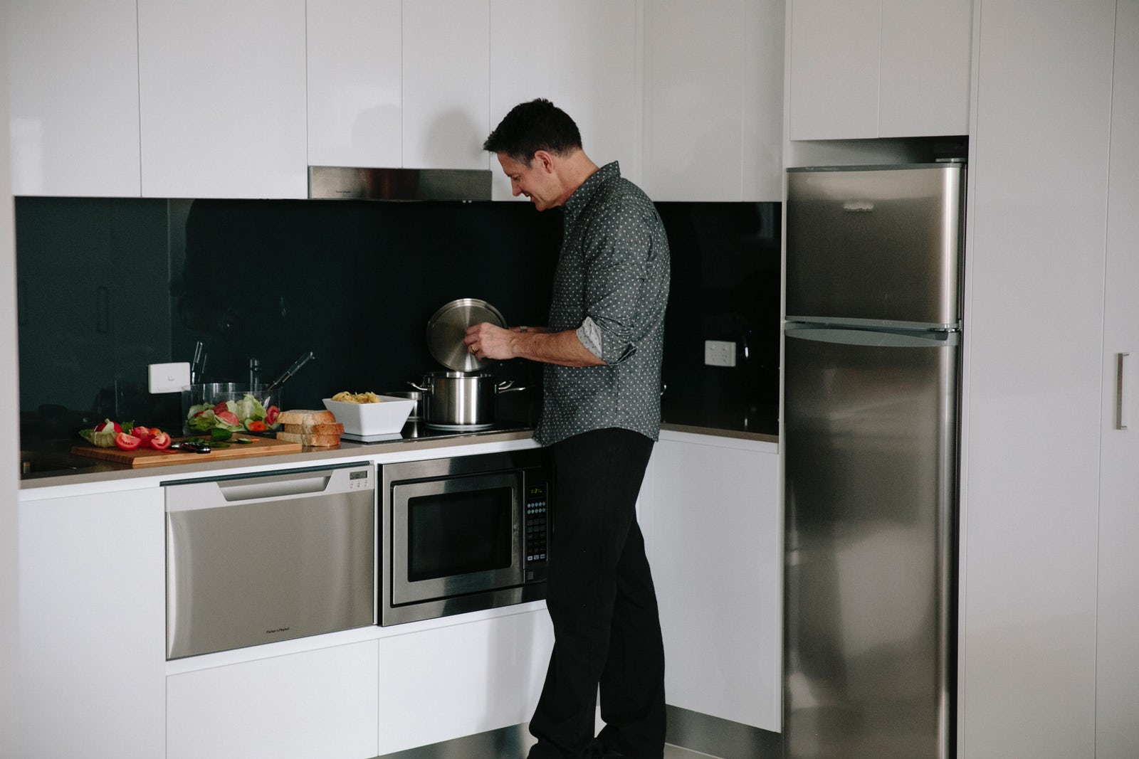 Picture of a man cooking in the Aria Hotel apartment in Canberra