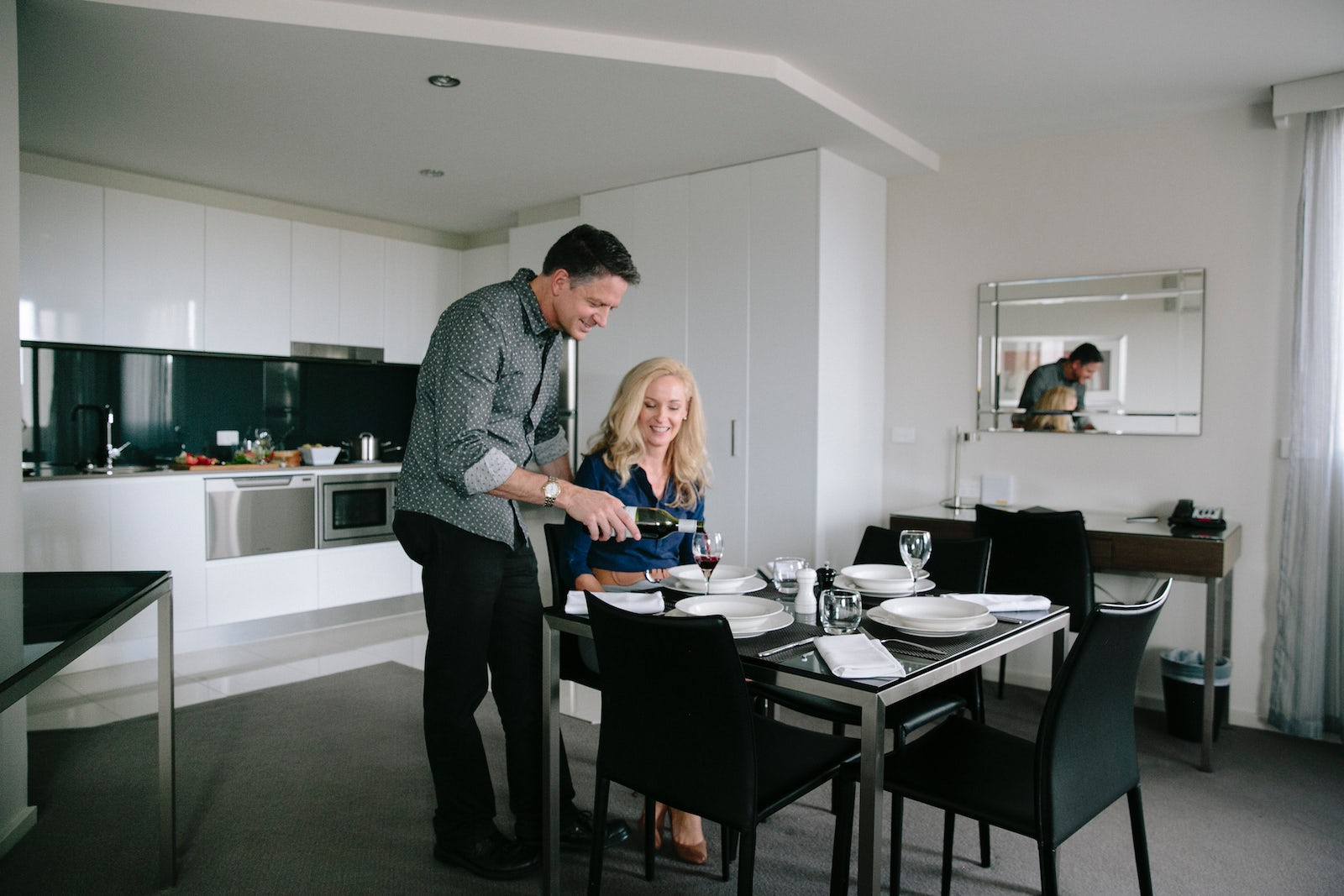 A picture of a man pouring a glass of wine in the Aria Hotel apartment located in Canberra