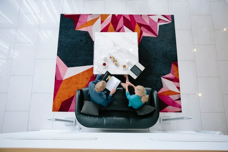 An Image of two people working in the waiting room at Aria Hotel on Dooring Street